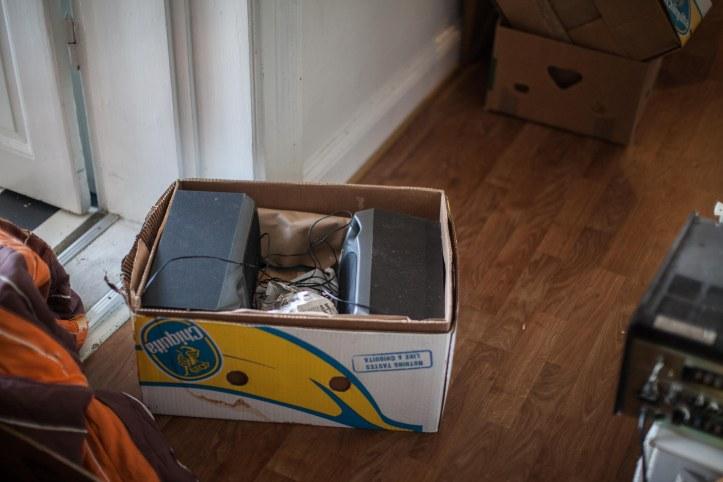Flyttlåda innehållande två högtalare, dörr karm, linoleumgolv, delar av fler lådor i bakgrunden, Fotograf: Karl Larsson. www.karllarsson.se